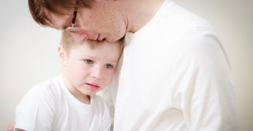 father comforting his crying little son - parenthood concept